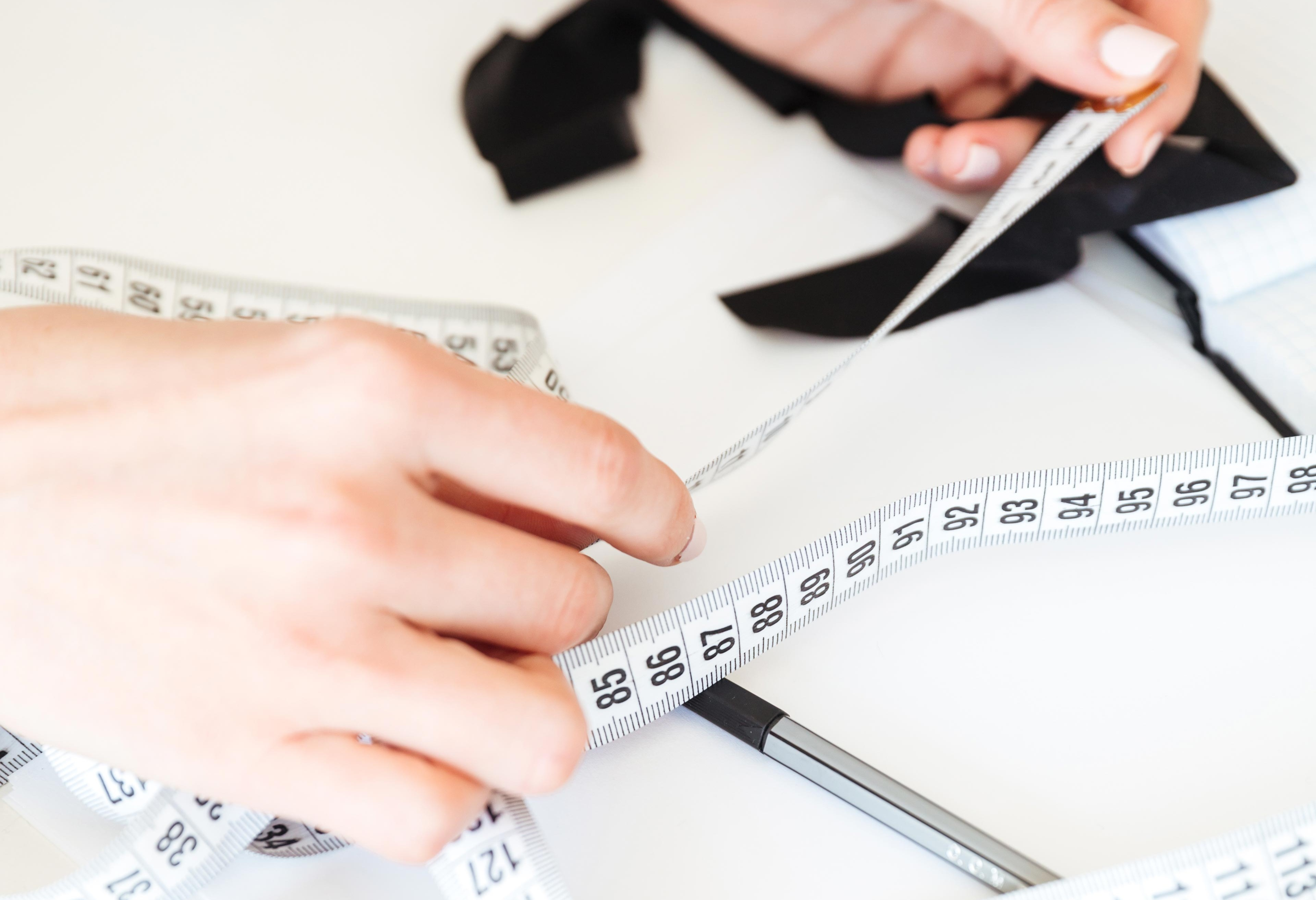 close-up-seamstress-working-with-measuring-tape